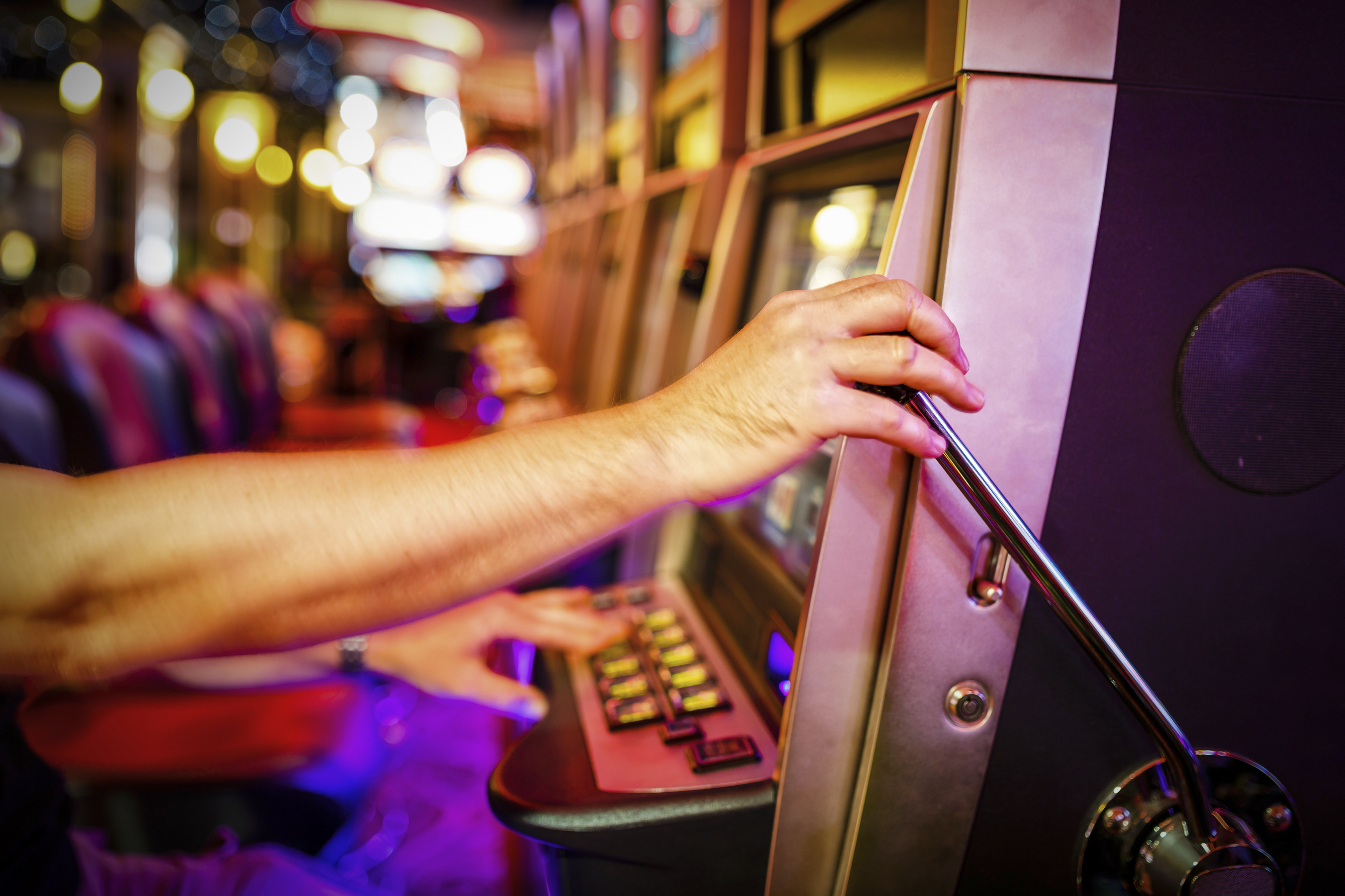 Man pulling down lever of slot machine in casino